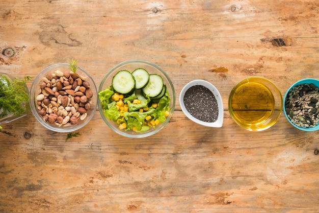 Elevated view of dryfruits; oil; chia seeds and ingredients arranged in a row on wooden table