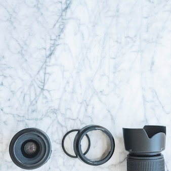 Elevated view of dslr camera with lens and extension rings on marble background