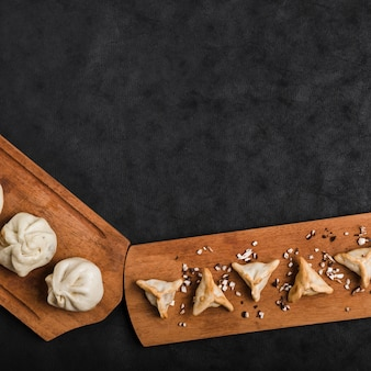 An elevated view of dumplings on wooden tray against black background