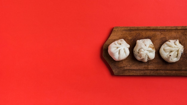An elevated view of dumplings on wooden tray against red backdrop