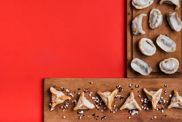 An elevated view of dumplings on wooden tray against red background