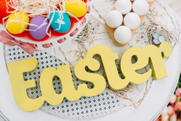 An elevated view of easter text with decorative colorful easter eggs on white table