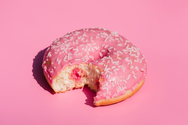An elevated view of eaten donut on pink background