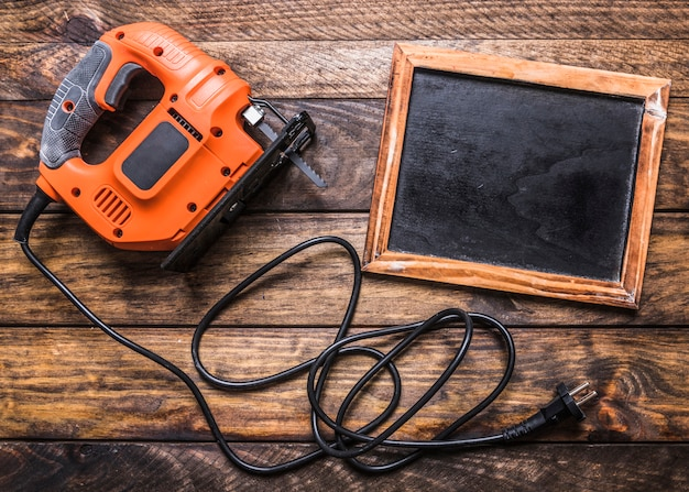 Elevated view of electric jigsaw and blank slate on wooden background