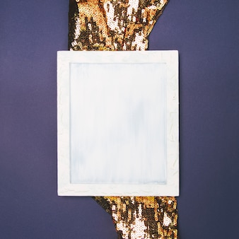 Elevated view of empty blank frame on golden sequin fabric against colored background
