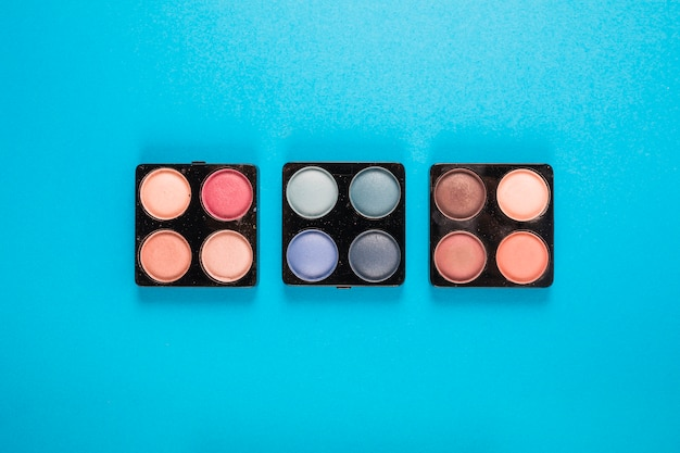 Elevated view of eye shadow powders on blue background