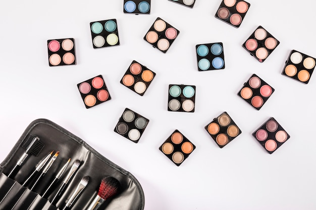 Elevated view of eye shadow powders and brushes on white backdrop