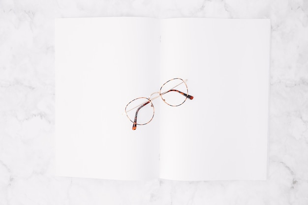 An elevated view of eyeglasses over blank white paper on marble background