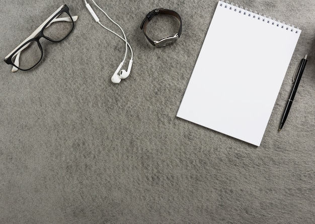 An elevated view of eyeglasses; earphone; wrist watch; spiral notepad and pen on gray desk