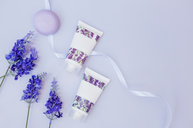 Elevated view of fake lavender flowers; soap; moisturizing cream and ribbon