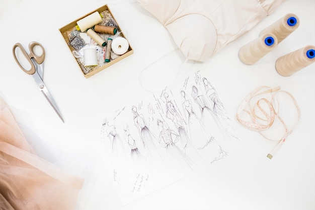 Elevated view of fashion sketch and sewing accessories on white background