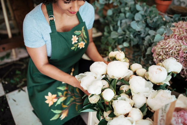 Elevated view of female florist arranging white peony flowers in shop