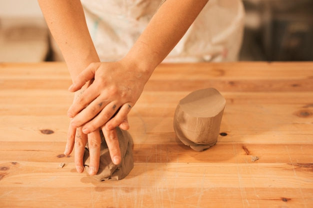 An elevated view of female kneading the clay on wooden table