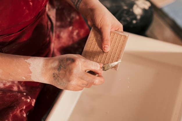 An elevated view of female potter cleaning the paint on tiles with sharp tool