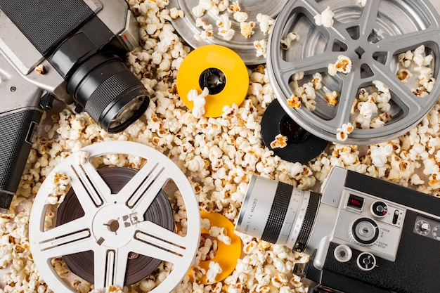 An elevated view of film reel; camera and camcorder over the popcorn