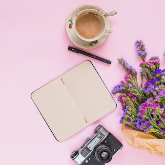 An elevated view of flower bouquet; vintage camera; diary; pen and coffee cup on pink background