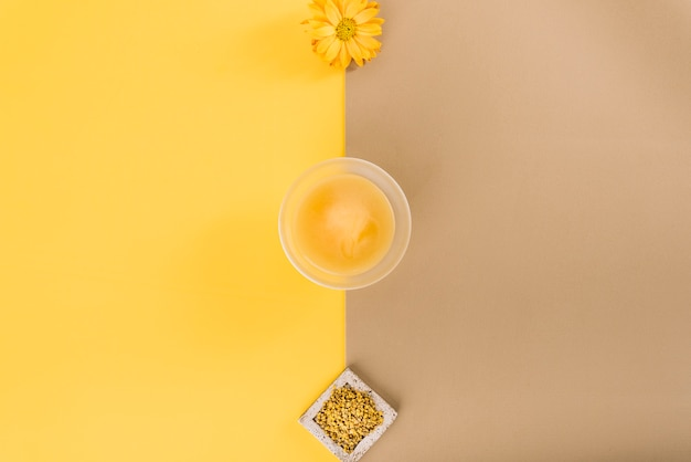 Elevated view of flowers; lemon curd and bee pollen on dual colored background