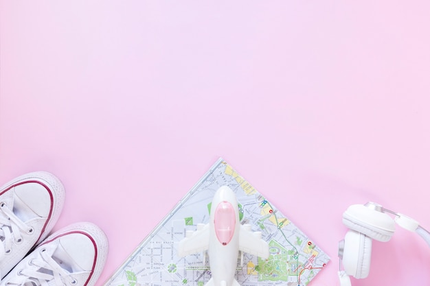 Elevated view of footwear; map; airplane and earphone on pink background