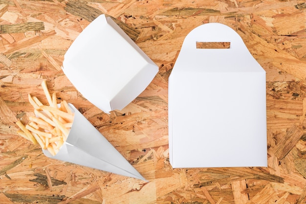 Elevated view of french fries and packages on wooden table