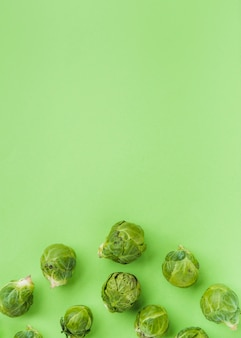 Elevated view of fresh brussels sprouts on green surface