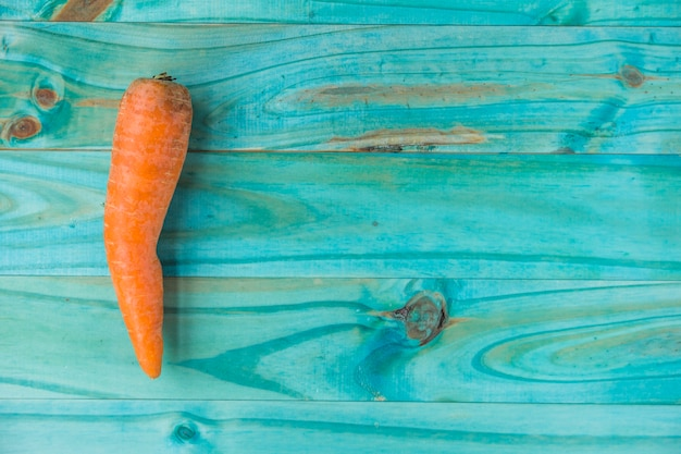 Elevated view of fresh carrot on turquoise colored wooden background