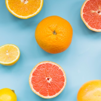 Elevated view of fresh citrus fruits on blue background