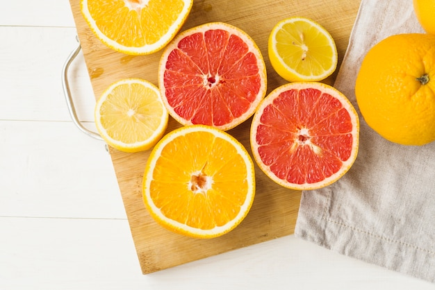Elevated view of fresh citrus fruits on chopping board
