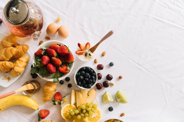Elevated view of fresh fruits; yogurt; egg and croissant on white backdrop
