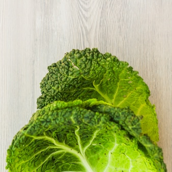 Elevated view of fresh green chinese cabbage leaves on wooden surface