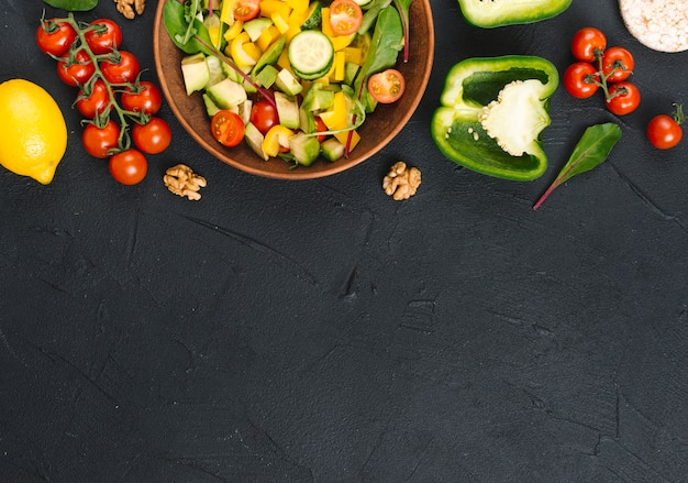 An elevated view of fresh healthy vegetable salad on black kitchen counter