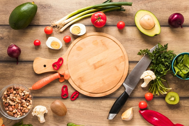 Elevated view of fresh ingredients; egg; vegetables and chopping board with knife on table