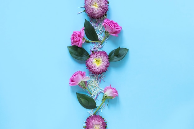 Elevated view of fresh pink flowers on blue surface