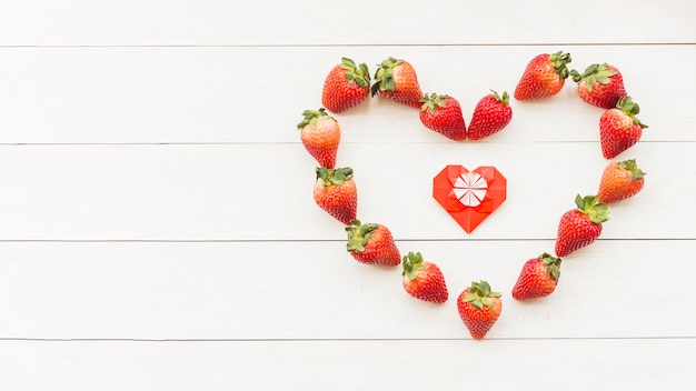 Elevated view of fresh red strawberries forming heart shape on wooden surface