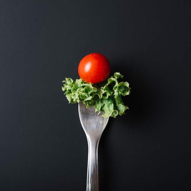 Elevated view of fresh tomato and lettuce with fork on black surface