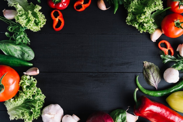 Elevated view of fresh vegetables forming circular frame on black background