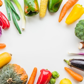 Elevated view of fresh vegetables forming circular frame on white backdrop