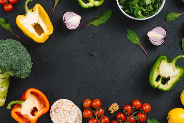 An elevated view of fresh vegetables and puffed rice cake on black concrete backdrop