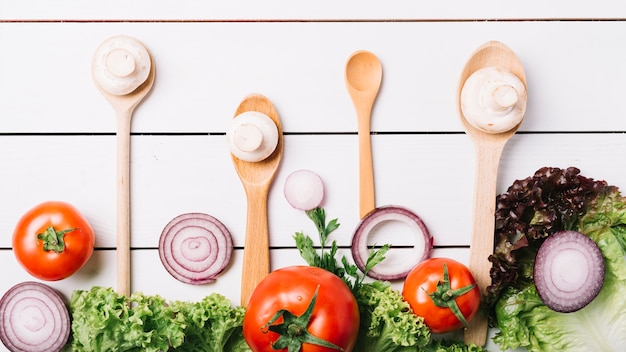 Elevated view of fresh vegetables with spoons on wooden background