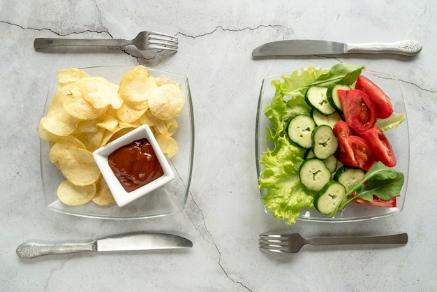 Elevated view of fried potato chips with sauce and vegetarian salad with knife and fork