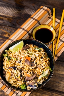 An elevated view of fried stir noodles with soya sauces and chopsticks on placemat