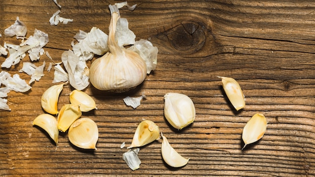 Elevated view of garlic cloves on wooden backdrop