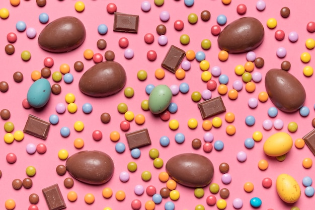 An elevated view of gem candies and chocolate easter eggs on pink background