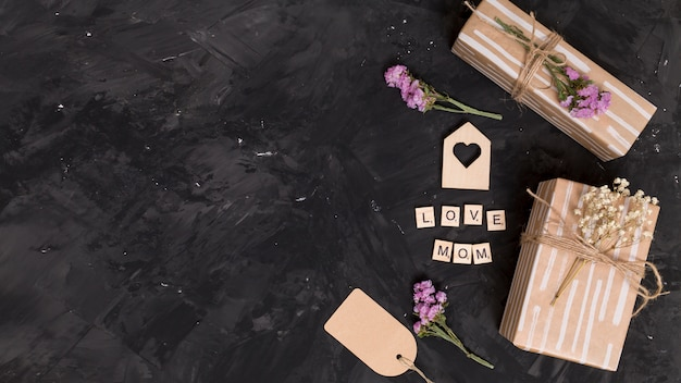 Elevated view of gift box; heart shape; flowers and price tag over black background
