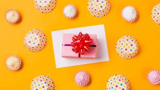 An elevated view of gift box on white paper with aalaw and polka dot paper cake forms on yellow backdrop
