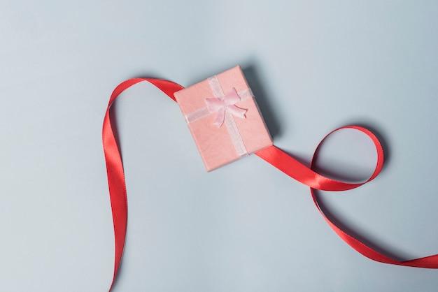 Vista elevata della confezione regalo con nastro rosso su sfondo grigio