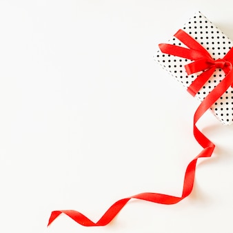 Elevated view of gift tied with red ribbon on white surface