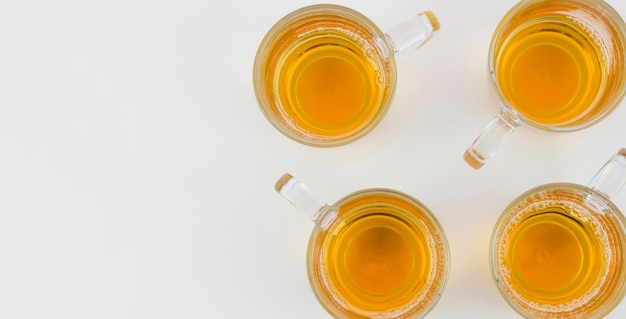 An elevated view of ginger tea in glass cups on white background