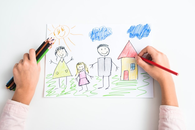 An elevated view of a girl's hand drawing the family and house with colored pencil on drawing paper