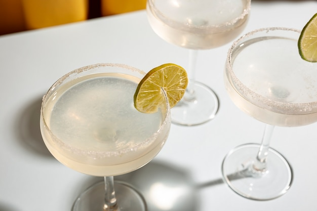 Elevated view of glass of margarita cocktail garnish with lime on table