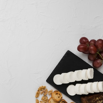 Elevated view of goat cheese slice on slate rock with grapes; bread and walnut over textured backdrop